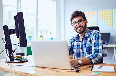 Man smiling using his laptop