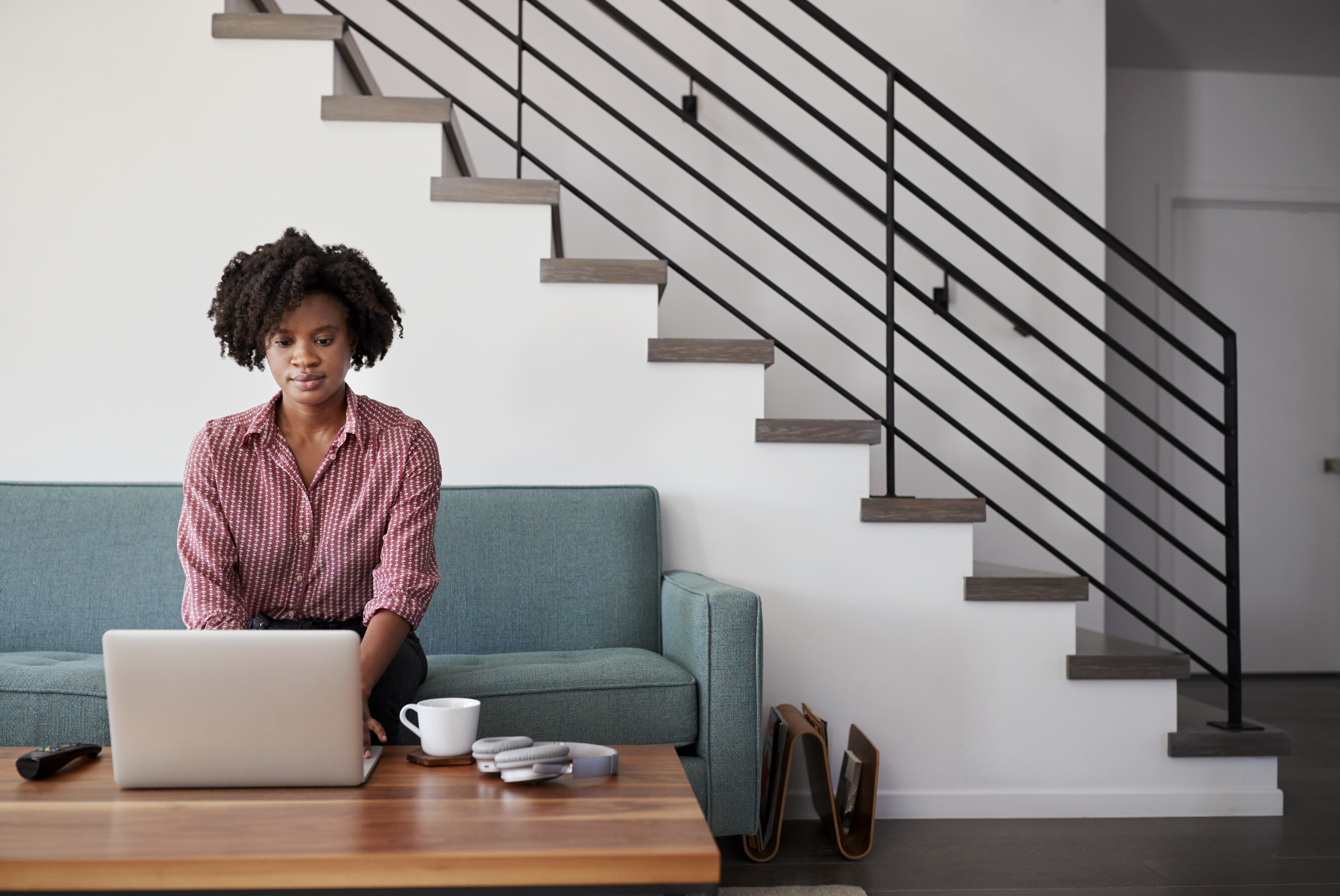 woman-sitting-on-sofa-at-home-using-laptop-compute-ENUBLVS